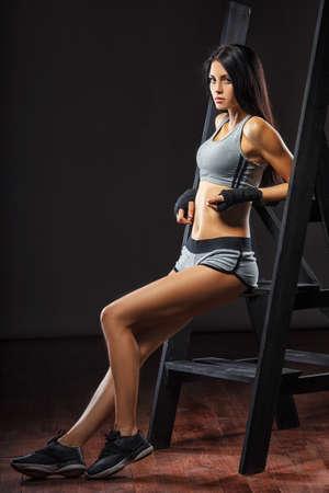 mujeres peleando: preciosa morena mujer boxeador de pie cerca de escalera sobre fondo oscuro larga duración Foto de archivo
