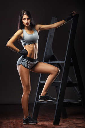 human sexual activity: beutiful brunette woman boxer standing near ladder over dark background full length