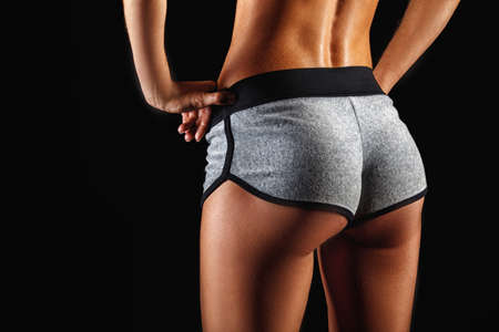 closeup woman beautiful buttocks over dark background