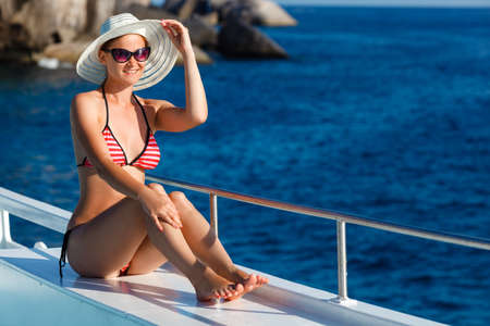 similan islands: woman in swimsuit sitting on board  and looking to a sea Stock Photo