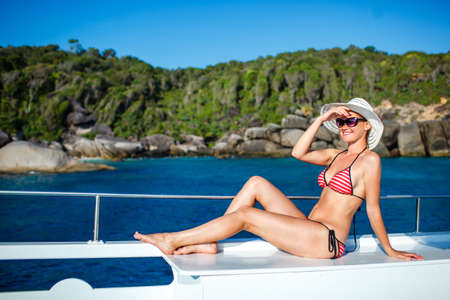 woman in swimsuit sitting on board  and looking to a sea photo
