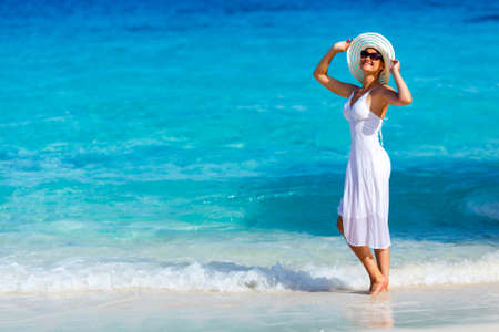 Young woman in a white dress walking on the tropical beautiful beach