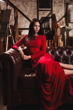 red sofa: elegant sensual young brunette woman in red dress sitting on leather sofa