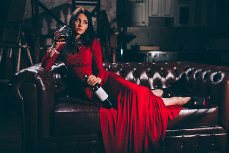 elegante sensuele jonge brunette vrouw in rode jurk zittend op lederen sofa, speciaal gestemde
