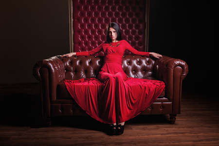 luxury lifestyle: elegant sensual young brunette woman in red dress sitting on leather sofa and looking at camera