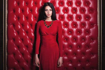 brunette woman: elegant sensual young brunette woman in red dress standing near wall
