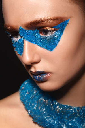 skintone: Fashion model with creative gold and blue makeup