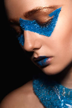 skintone: Fashion model with creative gold and blue makeup closed her eyes Stock Photo