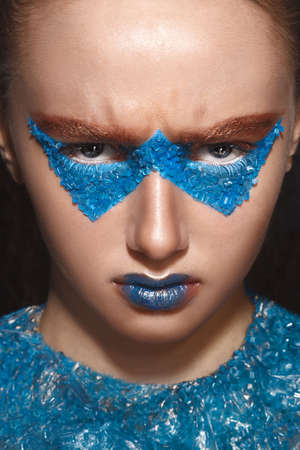 skintone: Fashion model with creative gold and blue makeup bend ones brows