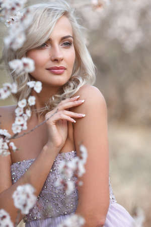 Beautiful blonde woman portrait in a flowered spring garden Stock Photo