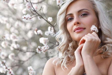 ragazza innamorata: Bella bionda donna di testa e spalle ritratto in un giardino fiorito di primavera