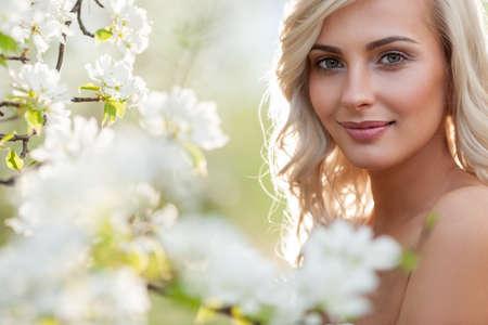 Beautiful blonde woman head and shoulders portrait in a flowered spring garden Standard-Bild