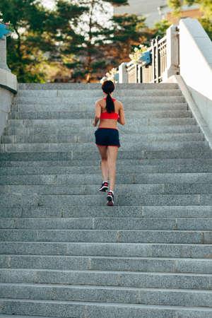 subir escaleras: Runner atleta correr en las escaleras de la ciudad. mujer de fitness trotar entrenamiento concepto de bienestar.