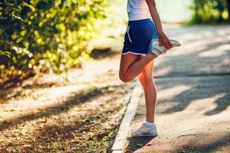 legs: yong mujer deportiva streching su pierna en el parque de verano Foto de archivo