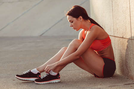 shoe model: brunette runner woman sitting on the ground and tie laces, sunset time, evening workout