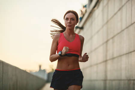 heart monitor: Girl runs along the concrete wall at sunset, wearing heart rate monitor