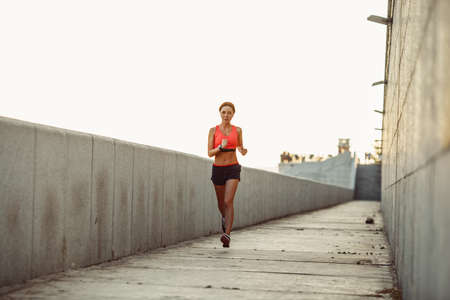 rate: Girl runs along the concrete wall at sunset, wearing heart rate monitor