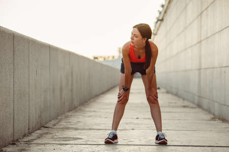 woman clothes: Young caucasian woman taking breath after jogging. Female athlete resting with hands on knees and looking away at sunset