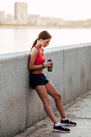 parapet: Female runner with bottled water tired from running standing near granite parapet Stock Photo