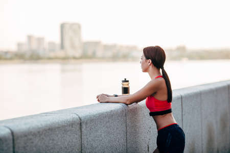 parapet: Female runner with bottled water tired from running standing near granite parapet, looking far away
