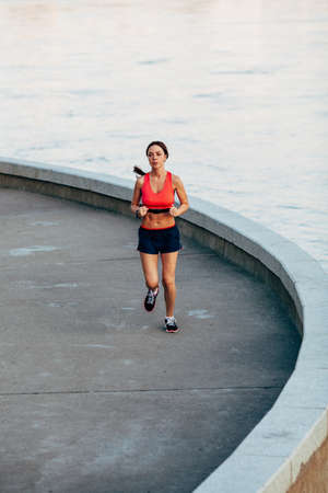 rate: sporty woman runnning along granite curved parapet