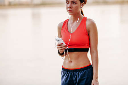 rate: Image of young woman taking a break form workout using mobile phone outdoors.