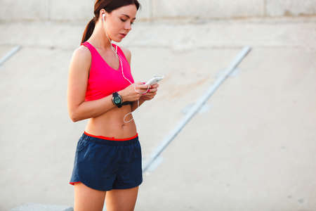 resting heart rate: Image of young woman taking a break form workout using mobile phone outdoors.