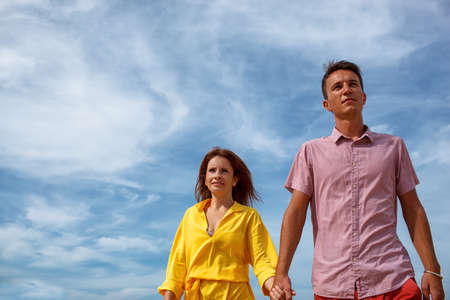 point of view: young adult couple walking under blue skies