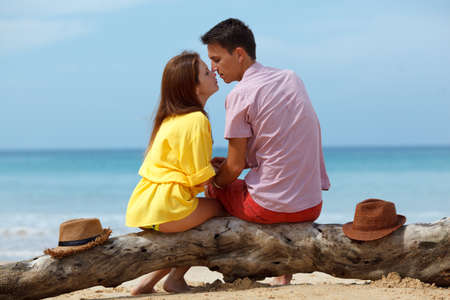 lovely couple: lovely couple sitting on a log at the beach