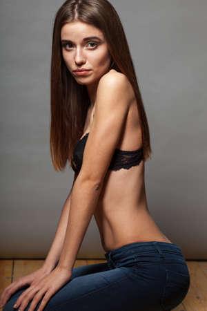 poses de modelos: Actitudes del modelo llevaba sujetador y jeans, ella está sentada en el suelo