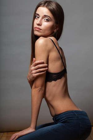 poses de modelos: Modelo de moda caucásica plantea llevaba sujetador y jeans, ella está sentada en el suelo