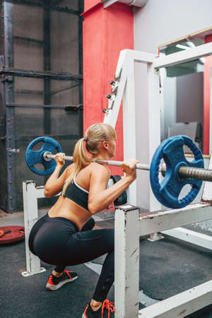 powerlifting: blonde strong fitness woman doing barbell squats in a gym