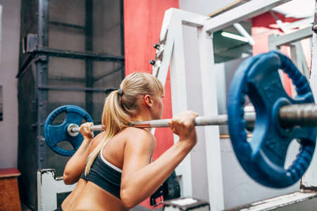WOMAN FITNESS: blonde strong fitness woman doing barbell squats in a gym