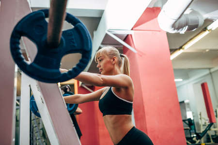 point of view: blonde strong fitness woman doing barbell squats in a gym, low point fo view Stock Photo