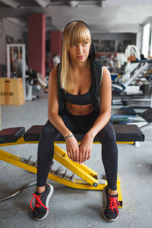 skinny woman: blonde athletic woman sitting on a bench  and resting in the gym