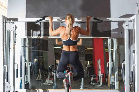 blonde vrouw uit te werken en het doen van een aantal pull-ups op een sportschool Stockfoto