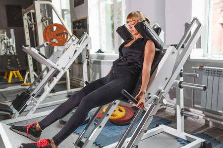 hack: Beautiful blonde fitness model workout, doing hack squat