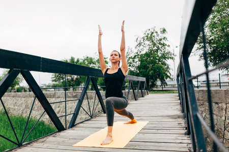 woman hands up: young slim woman doing yoga in the park on the wooden bridge Stock Photo