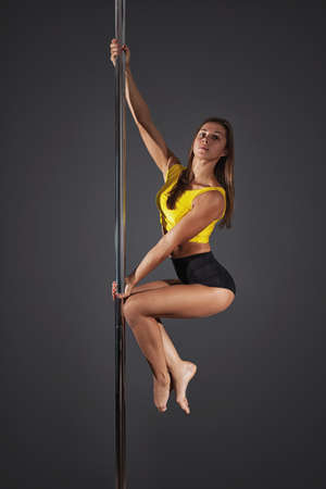 nude blonde girl: Young sexy woman exercise pole dance before a gray background