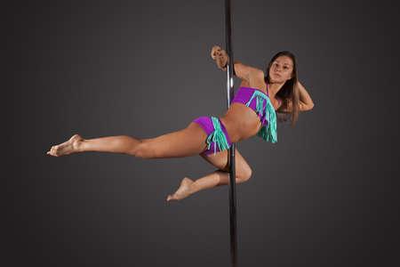 mujeres eroticas: Joven morena mujer sexy pole dance ejercicio antes de un fondo gris