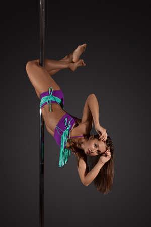 mujeres eroticas: Danza atractiva joven del poste del ejercicio de la mujer antes de un fondo gris