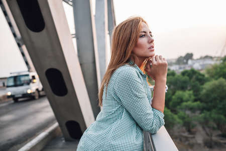 niña pensando: adulto yong bella mujer de pie en el puente y mirando de lejos Foto de archivo