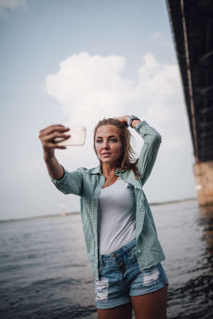 young adult woman: beautiful young adult woman taking picture of herself, selfie.
