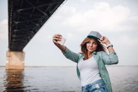 young adult woman: beautiful young adult woman taking picture of herself, selfie. She hold cap on her head