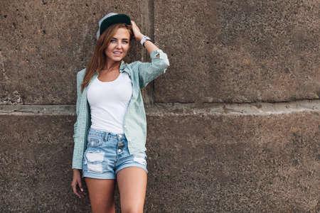 gingerish: fashion beautiful girl posing near concrete wall Stock Photo