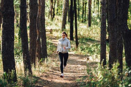 personas trotando: Corredor de la mujer caucásica activa en parque del otoño Foto de archivo