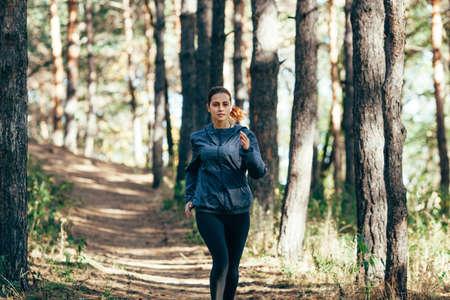outdoor fitness: runner caucasian woman wearing dark gray jacket jogging in autumn park