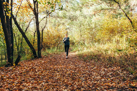 autumn colors: runner caucasian woman wearing dark gray jacket jogging in autumn park, overall plan