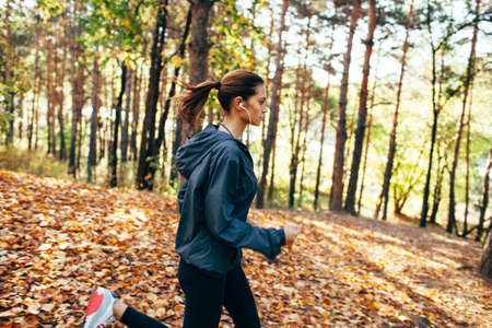 runner caucasian woman wearing dark gray jacket jogging in autumn park, right side view
