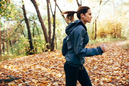 personas trotando: corredor caucásico mujer corriendo en el parque de otoño. Efecto de desenfoque de movimiento Foto de archivo